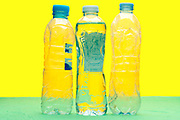 three clear plastic water bottles on yellow green background