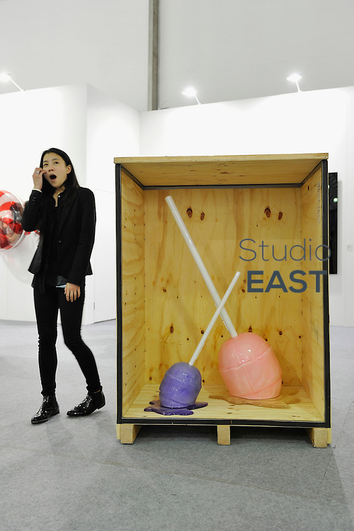 HONG KONG - MARCH 13: An exhibitor yawns next to a box with sculptures 'Medium Meltdown - Grape' (left) and 'Meltdown - Sugarcane Bubblegum' (right) by Desire Obtain Cherish in art fair Art Central on its first day on March 13, 2015 in Hong Kong, Hong Kong.  (Photo by Lucas Schifres/Getty Images)