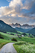 Views of the Geisler/Odle Group and a church in St. Magdalena (Santa Maddalena) village are iconic of the Dolomites mountains. See the valley and municipality of Funes (Villnöss) in Trentino-Alto Adige/Südtirol (South Tyrol), Italy. Enjoy great hiking here in the vast Nature Park of Parco Naturale Puez-Odle (German: Naturpark Puez-Geisler; Ladin: Parch Natural Pöz-Odles). The Dolomites are part of the Southern Limestone Alps, Europe. UNESCO honored the Dolomites as a natural World Heritage Site in 2009.