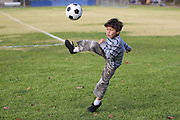 Young boy kicking a ball in a field