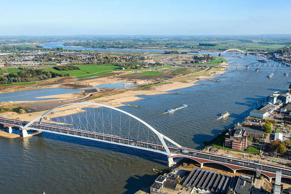 Nederland, Gelderland, Nijmegen, 24-10-2013; de nieuwe stadsbrug van Nijmegen over rivier de Waal, De Oversteek. Daarachter de spoorbrug met fietspad (De Snelbinder) en de laatste brug is de Waalbrug. Links van de rivier grondwerkzaamheden voor de Dijkteruglegging Lent (Ruimte voor de Rivier) en Nijmegen-Noord.<br /> First bridge the new city bridge of Nijmegen on the river Waal, De Oversteek (The Crossing). Next the railway bridge with cycle path (De Snelbinder = The Luggage strap) and finally the Waal bridge. To the left of the river groundwork for the Dike relocation of Lent (project Ruimte voor de Rivier: Room for the River). <br /> luchtfoto (toeslag op standaard tarieven);<br /> aerial photo (additional fee required);<br /> copyright foto/photo Siebe Swart.<br /> luchtfoto (toeslag op standaard tarieven);<br /> aerial photo (additional fee required);<br /> copyright foto/photo Siebe Swart.