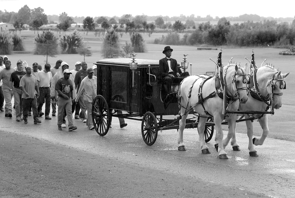 Lloyd Bone, a prisoner at Louisiana's State Penitentiary, rides atop a horse driven hearse carrying the body of fellow prisoner George Alexander, who died at the age of 56.  The hearse was hand built by prison carpenters. The elaborate funerals for inmates buried in the prison's cemetary is an example of how hospice volunteers, with the support of Warden Burl Cain, have created a tone of reverence for the dying and the dead at Angola Prison.
