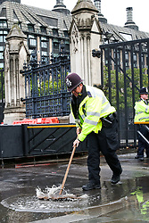 © Licensed to London News Pictures. 24/09/2019. London, UK. A police officer sweeps away puddle of rain water gathered at the gates of Houses of Parliament during heavy downpour in London. Photo credit: Dinendra Haria/LNP