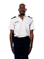 Portrait of a smart afro American police officer in uniform standing in studio on white isolated background
