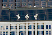 Three of Muriel Castanis' shrouded Corporate Goddesses stand in front of the mansard roof of 580 California Street, a 23-story building in San Francisco's Financial District.