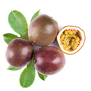 Passion fruit, whole and cut in half, on green leaves, isolated on white background. Top view, closeup shot.