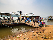11 MARCH 2016 - LUANG PRABANG, LAOS: People disembark a ferry after it crossed the Mekong River near Luang Prabang. Laos is one of the poorest countries in Southeast Asia. Tourism and hydroelectric dams along the rivers that run through the country are driving the legal economy.       PHOTO BY JACK KURTZ