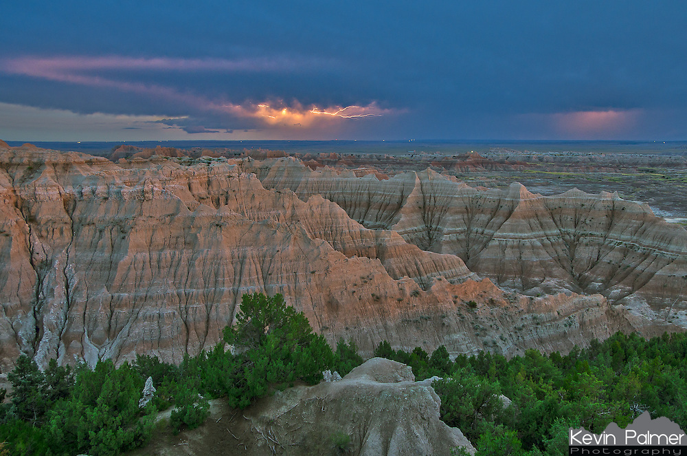 A distant lightning storm moves south past the Badlands National Park. The red sky in the west was casting a soft glow on the tops of the cliffs. The black dots in the center are turkey vultures.<br /> <br /> Date Taken: August 7, 2013