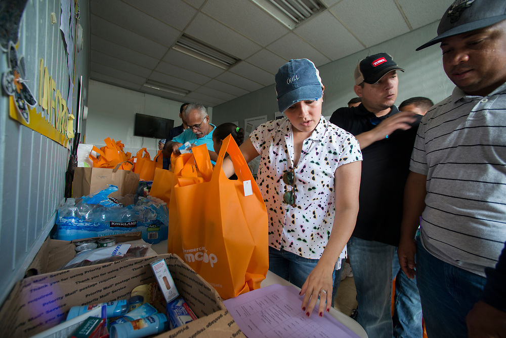 Comerio, PR, November 11, 2017--Carla Martinez, a law student from San Juan, volunteered to assemble packages of supplies that will be distributed to people in remote communities who have been hard hit by Hurricane Maria. The donated water, food, personal hygiene supplies and medical supplies were donated to Casa Juana Colon, a nonprofit that provided services for women survivors of domestic violence. Photo by Lori Waselchuk