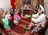 Alexandra Fay, Madeline Isabelle and Catherine Fay enjoy a special visit with Grandma Hamel and Nana Parkhurst along with a treat from Linda the Elf as they make their way through Laconia's Christmas Village Thursday evening.  (Karen Bobotas/for the Laconia Daily Sun)