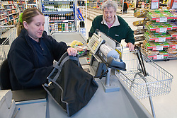 Woman at supermarket checkout assisting packing shopping bags for customer,
