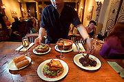 Zuzu Restaurant, Napa, California. Napa Valley. Zuzu serves tapas: small plates of food to accompany a drink. On the bar, with two glasses of sherry, (foreground, clockwise) queso frito: pan fried Manchego cheese with roasted poblano chiles; roasted spaghetti squash with apple cider syrup and midnight moon cheese; leblebi: garbanzo bean soup, roasted peppers, poached eggs and harissa; Moroccan barbecue glazed lamb chops.