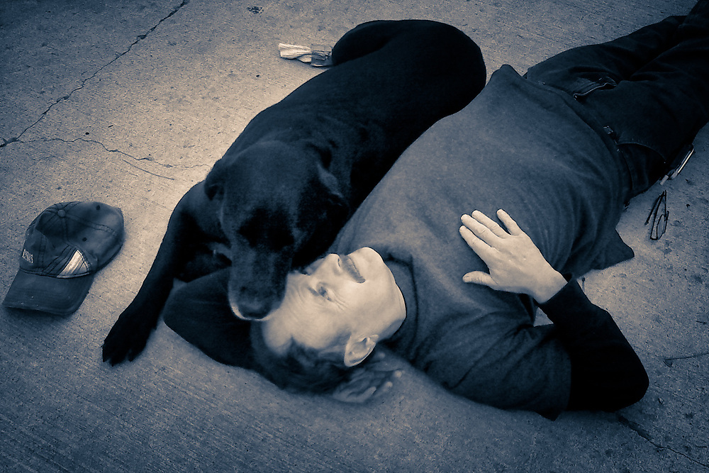 Terry Everhardt and his dog Gunther laying on the concrete driveway