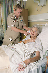 Auxiliary nurse with elderly female patient using a Tympanic thermometer,