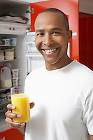 Man holding glass of orange juice, by fridge, portrait