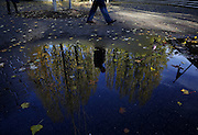 A man walking near Husky Stadium passes a reflection of the first blue skies seen in days, after an abundance of Seattle rain temporarily subsides.<br />