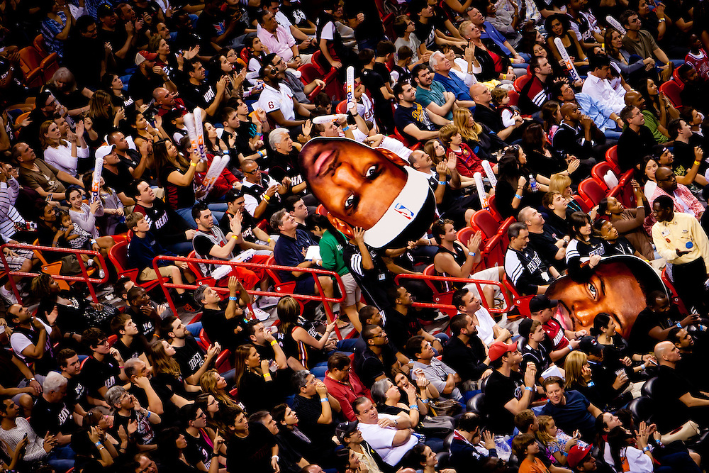 MIAMI, FL -- January 29, 2012 -- Miami fans cheer their team on with large headshots of Lebron James, Dwyane Wade, and Chris Bosh during the Heat's 97-93 win over the Chicago Bulls at American Airlines Arena in Miami, Fla., on Sunday, January 29, 2012.  (Chip Litherland for ESPN the Magazine)