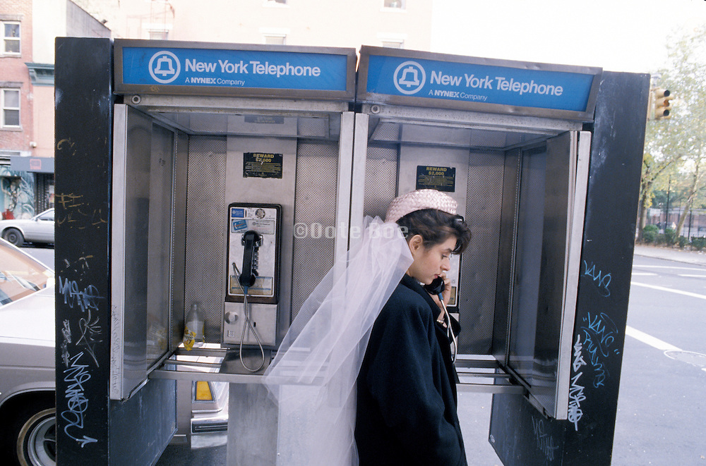 bride making a call at a pay phone