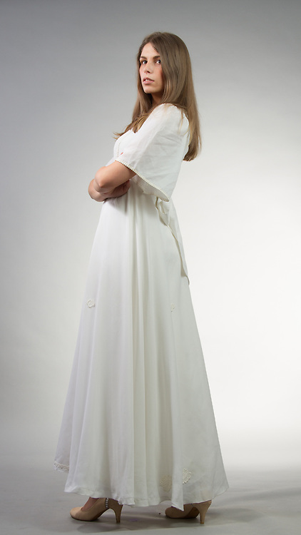 Female model posing in a white dress.