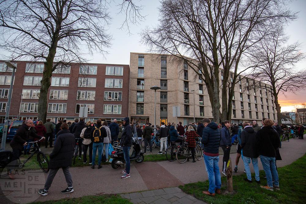 Omstanders staan bij de woning aan de Oudenoord in Utrecht waar de verdachte van de schietpartij in de tram in Utrecht is aangehouden.