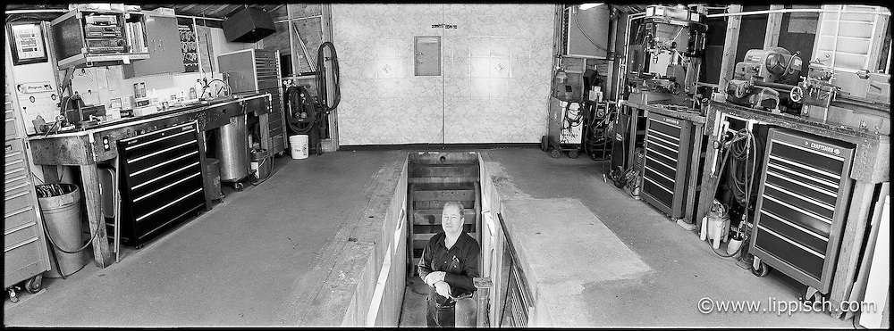 A mechanic stands in the pit of his home made auto garage.