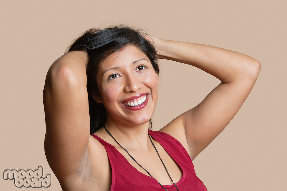 Beautiful young woman with hands in hair over colored background
