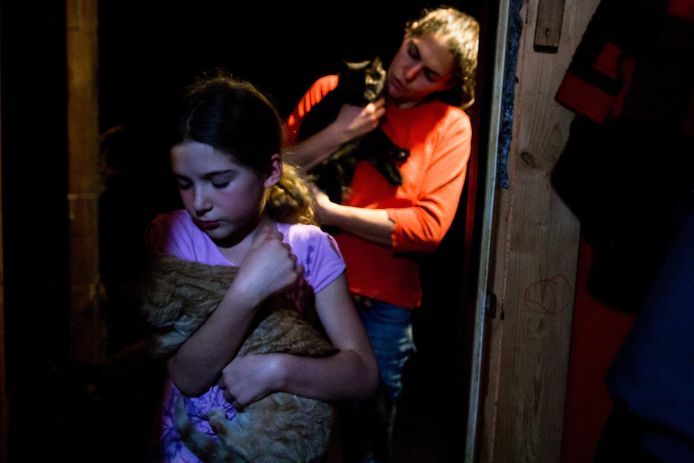 Kate Marsiglio and her daughter, Lucia, 8, cuddle their cats before bedtime in the farmhouse. Lucia and her brother are homeschooled by their grandmother, who lives nearby in the original Stony Creek farmhouse. The opportunity to keep family close was a large part of Kate and Dan's decision to start farming.