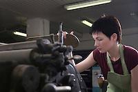 Young woman operating printing press