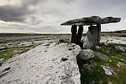 Burren, County Clare. Poulnabrone Dolmen is a portal tomb  dating back to the Neolithic period, probably between 4200 BC to 2900 BC. It is situated 8km south of Ballyvaughan. The dolmen consists of a twelve-foot, thin, slab-like, tabular capstone supported by two slender portal stones, which lift the capstone 1.8m from the ground, creating a chamber.<br /> The tomb was likely a centre for ceremony and ritual until well into the Celtic period or it may have served as a territorial marker in the Neolithic landscape.