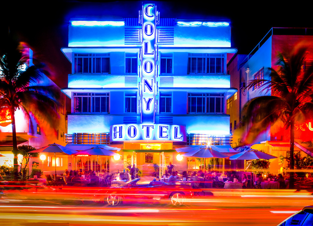 The neon-lit, Art Deco-style Colony Hotel and sidewalk cafe at night on Miami Beach's Ocean Drive in South Beach, with a red Ferrari parked in front.The hotel was designed by architect Henry Hohauser in 1935