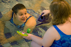 Care Worker talking to a Day service user with learning disability who is playing with a watering can at the local swimming pool,