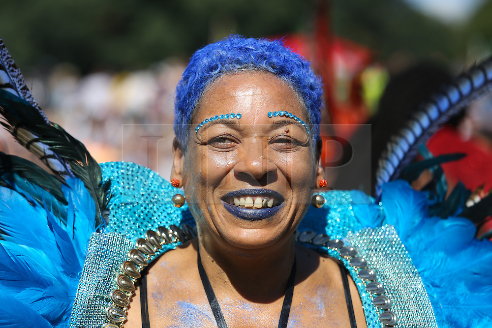 © Licensed to London News Pictures. 29/08/2016. Leeds, UK. A smiling woman wears a colourful costume at Leeds West Indian Carnival in Leeds, West Yorkshire. First run in the 1960's, the Leeds West Indian Carnival is Europe's longest running authentic Caribbean carnival parade. Photo credit : Ian Hinchliffe/LNP