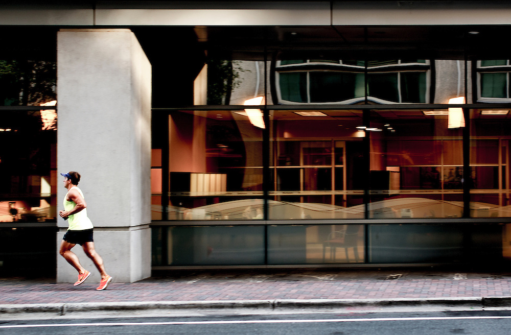 Male athlete running down a sidewalk in an urban area.