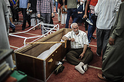 60360670 <br /> An Egyptian leans beside a coffin at a mosque where lines of bodies wrapped in shrouds were laid out in Cairo, Egypt, August 15, 2013. At least 525 were killed and 3,717 others injured across Egypt in clashes between supporters of ousted President Mohamed Morsi and the security troops, after the latter dispersed Wednesday two major pro-Morsi sit-ins in Cairo and Giza, a Health Ministry official said Thursday, August 15, 2013. <br /> Picture by imago / i-Images<br /> UK ONLY
