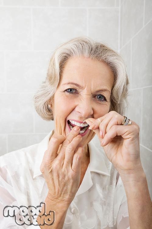 Portrait of senior woman flossing teeth in bathroom