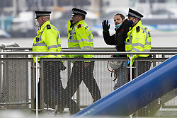 © Licensed to London News Pictures. 25/07/2020. London, UK. An Extinction Rebellion activist waves as he is arrested after he locked himself to a drilling rig in the Thames close to the 02 Arena in Greenwich this morning . The rig is involved with preparatory drilling for the Silvertown Tunnel which is planned to connect the Greenwich Peninsula with west Silvertown. Extinction Rebellion oppose the building of the tunnel due to the increase in air pollution it may cause. Photo credit: George Cracknell Wright/LNP