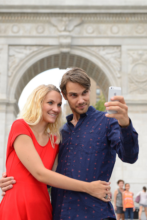 Couple taking sefie image on Washington Square, New York, Manhattan, USA<br /> Model release 0340,0341
