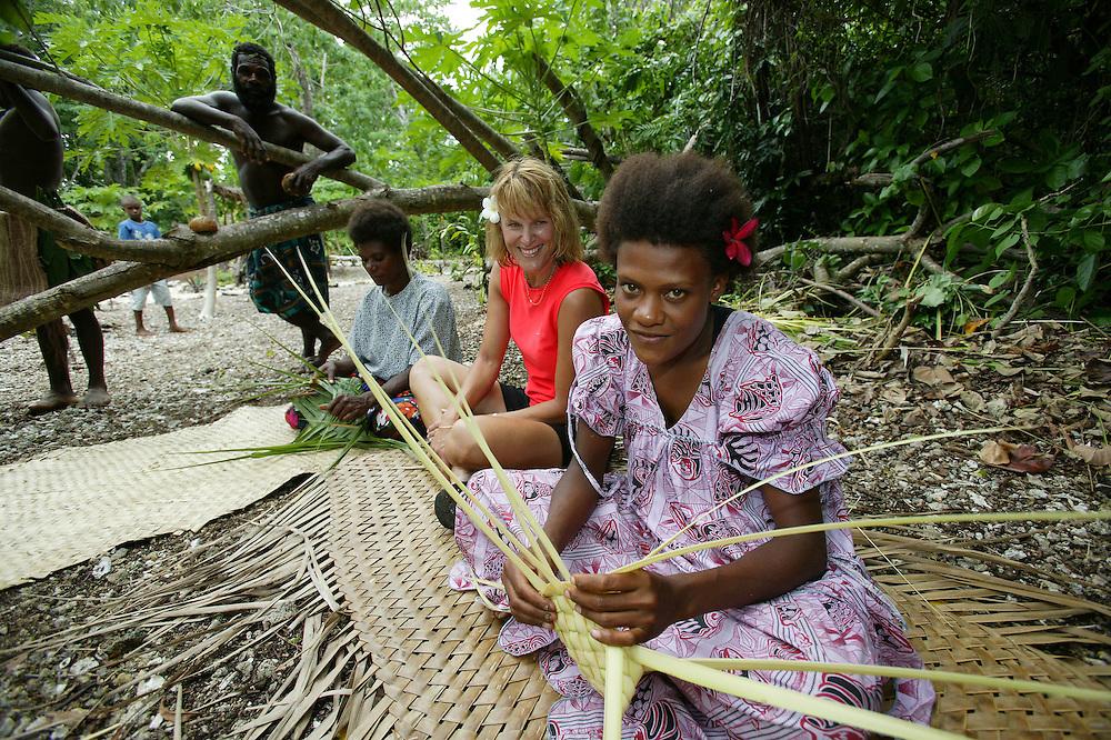 Eratap native villagers show a tourist the art of weaving, Port Vila, Vanuatu, January 30, 2006. Credit:SNPA / Rob Tucker