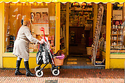 Een vrouw loopt met haar hondje in de mand van de rollator door Utrecht.<br /> <br /> A woman is walking with her dog is a basket at the center of Utrecht.