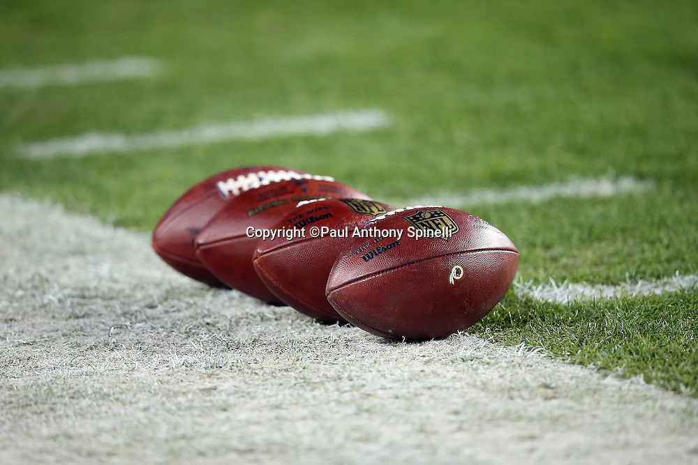 Four footballs lie on the sideline grass before the Washington Redskins 2015 week 13 regular season NFL football game against the Dallas Cowboys on Monday, Dec. 7, 2015 in Landover, Md. The Cowboys won the game 19-16. (©Paul Anthony Spinelli)