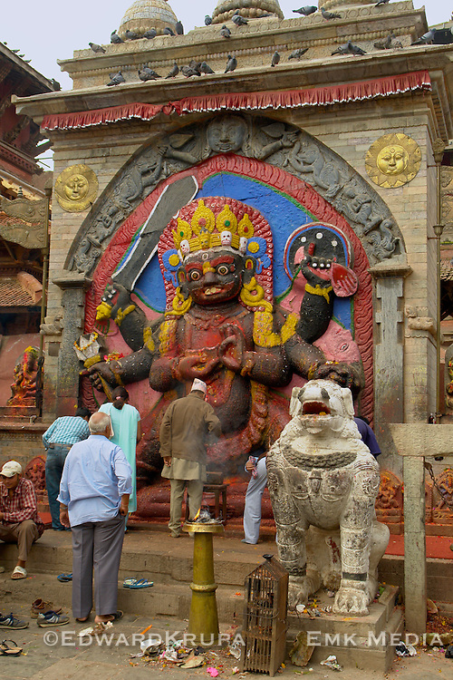 Image of a people offering prayers to Black (Kala) Bhairav relief at UNESCO's World Heritage Site of Kathmandu Durbar Square, Nepal,shows Shiva,the Hindu god of desruction and creation, in his most fearsome form. He has six arms, carries weapons and a body, has a headdress of skulls, and tramples a corpse.