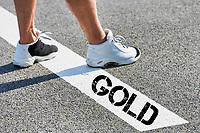 Man standing on white line with gold winner sign