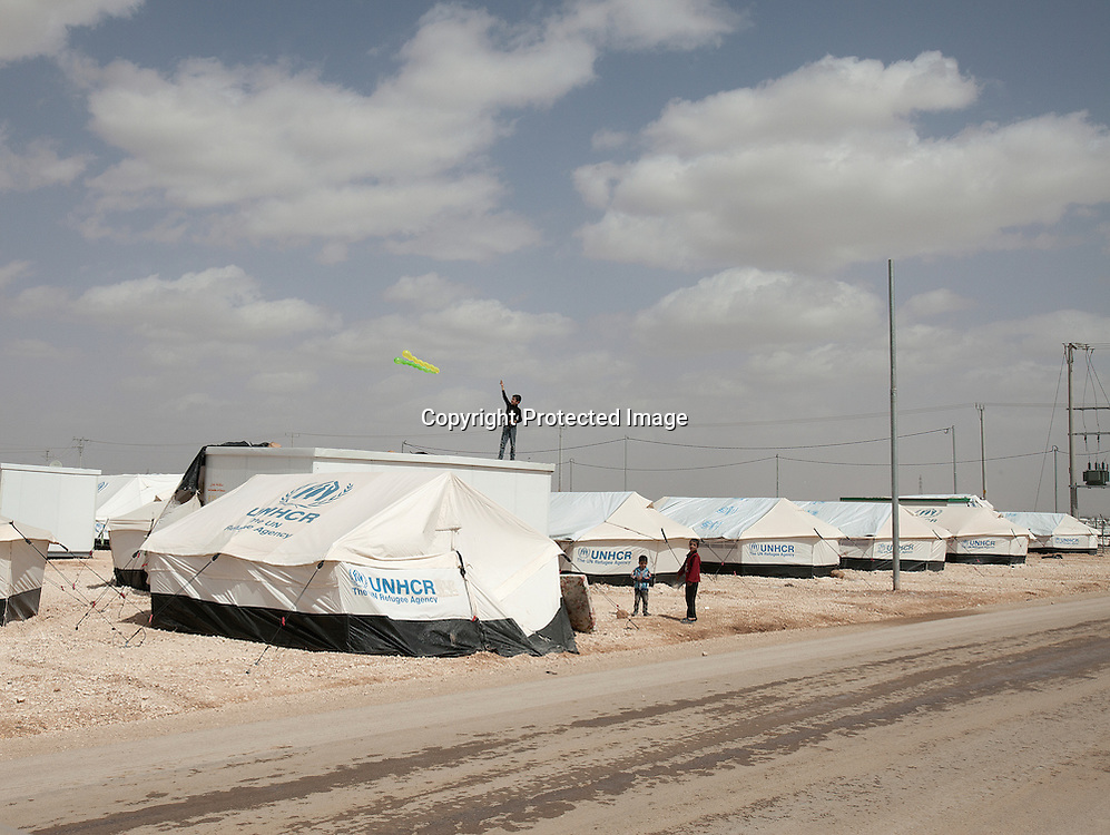 Young Syrian refugee flying a kite on the roof top of a countainer in Zaatari Refugee Camp located in Mafraq, Jordan