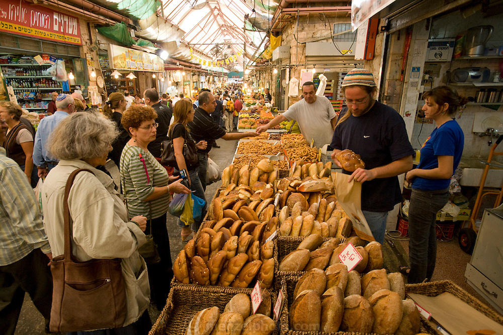 People shop for bread and other items at the Shuk Machaneh Yehuda, a large market in Western Jerusalem, Israel.