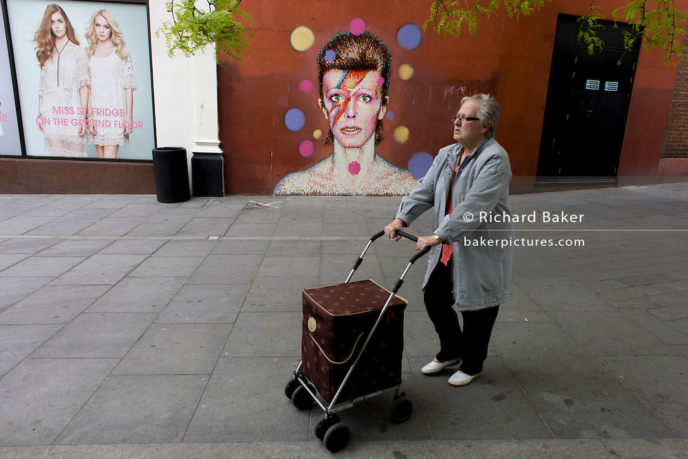 An elderly lady walks past the new mural of iconic musician and singer David Bowie has appeared on the wall of Morleys department store in Brixton, Lambeth, south London. The Bowie face is sourced (by artist James Cochran, aka Jimmy C) from the cover of his 1973 album Aladdin Sane at the height of his 1970s fame. The pop icon lived at 40 Stansfield Road, Brixton, from his birth in 1947 until 1953. This cover appeared in Rolling Stone's list of the 500 greatest albums of all time, making #277.