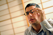 "Jake Adelstein, a former reporter at Japan's largest daily newspaper, Yomiuri Shimbun, and author of the recently released ""Tokyo Vice"" speaks  during an interview at an undisclosed location in Japan on Aug. 29, 2008. In 2005, American Adelstein  uncovered a scandal involving senior members of Japan's mafia, the yakuza, visiting a medical center in Los Angeles to undergo liver transplants, despite being bared from entry due to having criminal records or suspected affiliation with Japanese organized crime groups. Within days, however, Adelstein was visited by mob members and told to either ""erase the story or be erased."" He erased the story and resigned from the Yomiuri, though a leak of his story at one time pushed Adelstein and his family into hiding..Photographer: Robert Gilhooly"