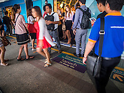 28 OCTOBER 2014 - BANGKOK, THAILAND:  Passengers get off and on the Skytrain at the Saphan Taksin station. The Skytrain (called the BTS) system has a combined length of 36 kilometres and includes 34 stations, including Saphan Taksin. While there are two train tracks for most stretches of the Skytrain system, the portion on the Saphan Taksin Bridge spanning the Chao Phraya River has just one track due to limited space, causing a bottleneck when an outbound train and inbound train arrive at the bridge at the same time. The Bangkok Metropolitan Authority (BMA) had sought permission from the Department of Rural Roads to expand the Taksin Bridge in order to make way for an additional track, but the department had said it was not possible. The Saphan Taksin  station was originally supposed to be temporary and is one of the busiest on the system. It's a connecting station for the Chao Phraya River boats used by Thai commuters coming into the city from neighboring provinces and tourists who use the boats to go upriver into the old parts of Bangkok from the central business district. More than 4,000 commuters a day use the station. The BMA plans to build an elevated moving sidewalk to the river from Surasak BTS station about one kilometer away. Surasak is the nearest station to Saphan Taksin. The Skytrain system has a combined length of 36 kilometres and includes 34 stations, including Saphan Taksin.       PHOTO BY JACK KURTZ