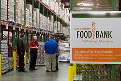 God's Pantry COO Manuel Howard, center, talks with potential donors in the warehouse, Thursday, April 13, 2017 at God's Pantry Food Bank in Lexington.