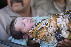 © Licensed to London News Pictures. 15/06/2017. Mosul, Iraq. A one day old baby, born yesterday (14/06/17) in ISIS held West Mosul is held up by Iraqi soldiers who are transporting her and her family to safety outside the city.<br /> <br /> Despite heavy fighting between the Islamic State and Iraqi Security Forces many civilians have started to leave ISIS territory in West Mosul. Mosul residents, many of whom have been in hiding in their homes since the start of the West Mosul Offensive, often have to run through ISIS sniper and machine gun fire to reach the safety of Iraqi Security Forces positions. Photo credit: Matt Cetti-Roberts/LNP