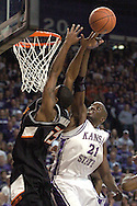 Kansas State forward Dramane Diarra (R) blocks Oklahoma State's Torre Johnson (L) in the first half at Bramlage Coliseum in Manhattan, Kansas, February 4, 2006.  The Cowboys and Wildcats are tied at halftime at 30-30.